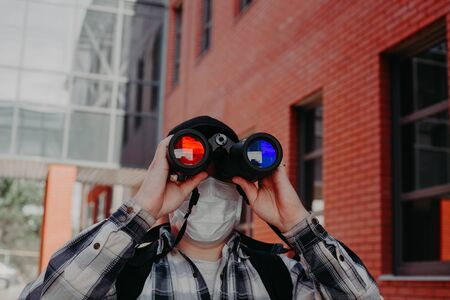 a guy looks through binoculars with different glasses in the center of the city. 스톡 콘텐츠