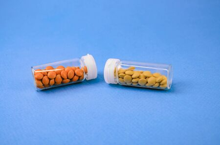 two glass packages with yellow and orange tablets lying with each other. on a blue background.