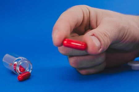 a man's hand is holding a red pill.