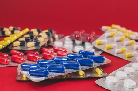 pile of multicolored tablets on a red background. 스톡 콘텐츠