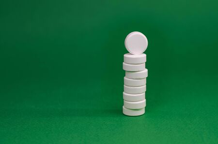 tower of white tablets on a green background. 스톡 콘텐츠