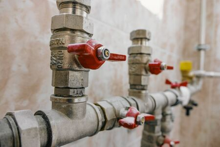 fittings and valve, pipes and adapters. Plumbing fixtures and piping parts. focus on the red crane.