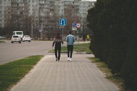 two friends are walking along a road in the city.