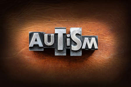The word Autism made from vintage lead letterpress type on a leather background.