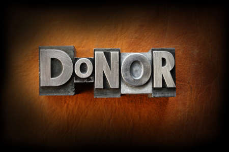 The word donor made from vintage lead letterpress type on a leather background. Фото со стока