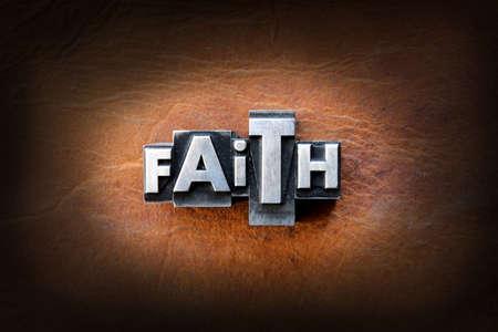 レザーの背景にビンテージ リードタイプ活版から作られた単語の信仰。 写真素材