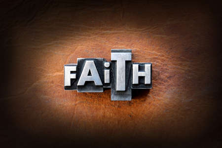 The word faith made from vintage lead letterpress type on a leather background. Zdjęcie Seryjne
