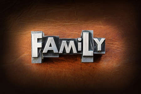 The word family made from vintage lead letterpress type on a leather background. Stock Photo