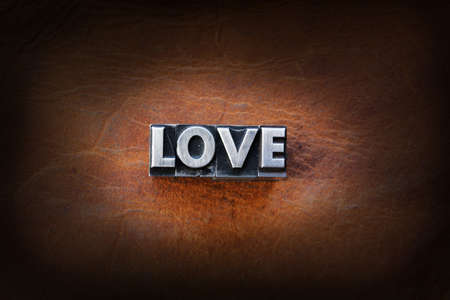The word love made from vintage lead letterpress type on a leather background.
