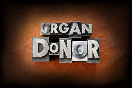 The words organ donor made from vintage lead letterpress type on a leather background.