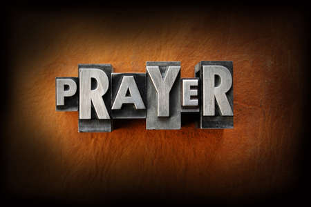The word prayer made from vintage lead letterpress type on a leather background. Imagens