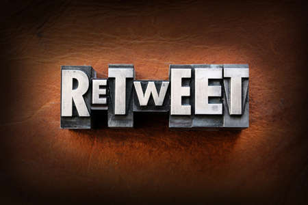 The word retweet made from vintage lead letterpress type on a leather background.