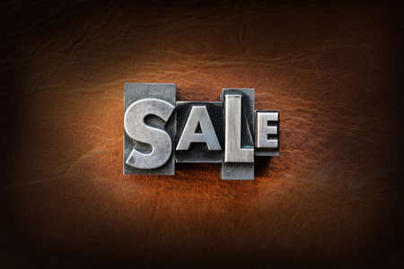 The word sale made from vintage lead letterpress type on a leather background. photo