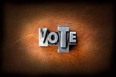 The word vote made from vintage lead letterpress type on a leather background. photo