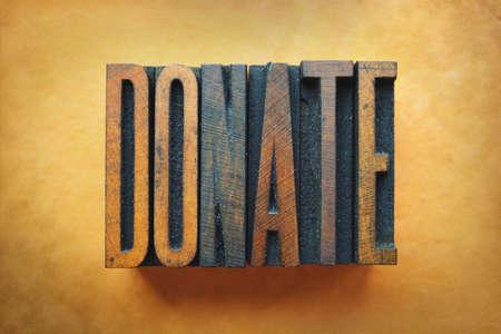 The word DONATE written in vintage letterpress type. Stock fotó