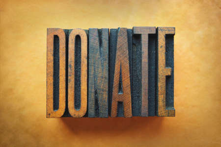 non: The word DONATE written in vintage letterpress type. Stock Photo
