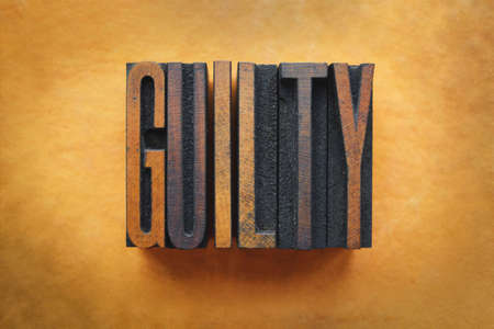 an inmate: The word GUILTY written in vintage letterpress type.