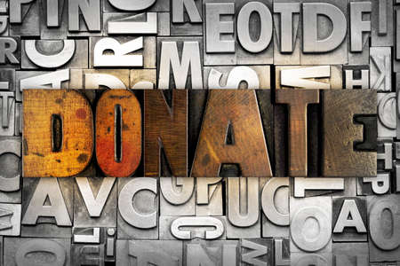 The word DONATE written in vintage letterpress type photo