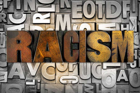 bigotry: The word RACISM written in vintage letterpress type