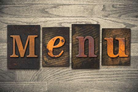 """Het woord """"MENU"""" geschreven in houten letterzetseltype."""