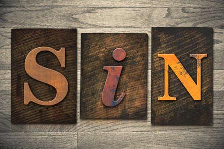 transgression: The word SIN written in wooden letterpress type.