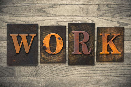 servitude: The word WORK written in wooden letterpress type.