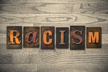bigotry: The word RACISM written in wooden letterpress type.