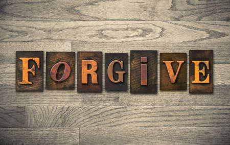 flaw: The word FORGIVE written in vintage wooden letterpress type. Stock Photo