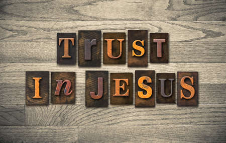The words TRUST IN JESUS written in vintage wooden letterpress type.