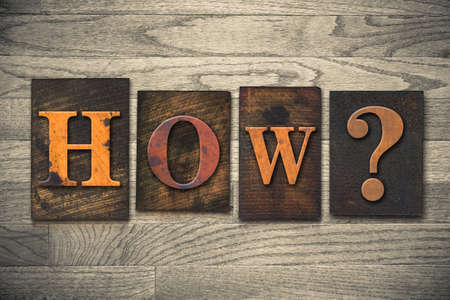 The word HOW? written in vintage wooden letterpress type. photo