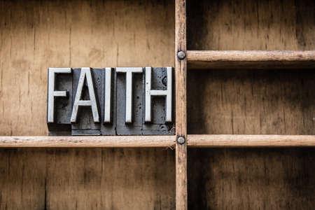 単語「信仰」は木製の引き出しに座ってビンテージ金属製凸版型で書かれました。 写真素材