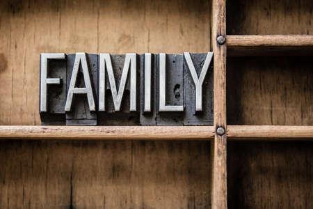 """arbol geneal�gico: La palabra """"FAMILIA"""" escrito en cosecha de metal tipo de tipograf�a de estar en un caj�n de madera. Foto de archivo"""