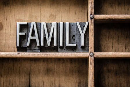 The word FAMILY written in vintage metal letterpress type sitting in a wooden drawer. Banco de Imagens