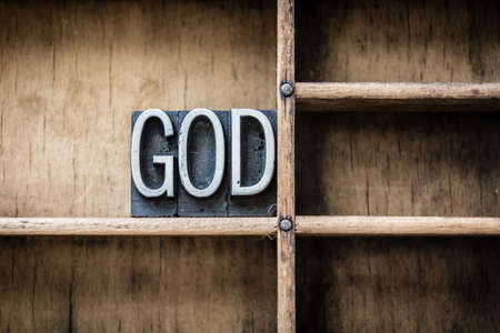 The name GOD written in vintage metal letterpress type sitting in a wooden drawer.