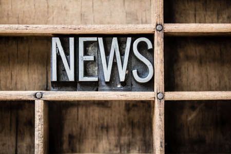 The word NEWS written in vintage metal letterpress type sitting in a wooden drawer.