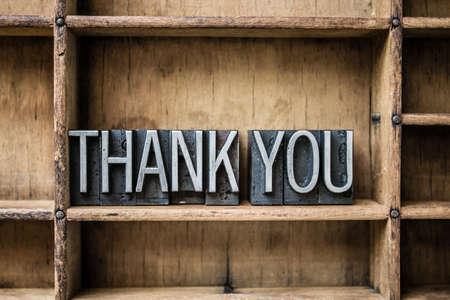 木製引き出しの中に座っているヴィンテージの金属活版型で書かれた「ありがとう」の言葉。