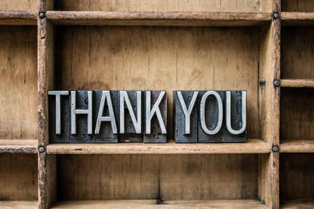 The words THANK YOU written in vintage metal letterpress type sitting in a wooden drawer.
