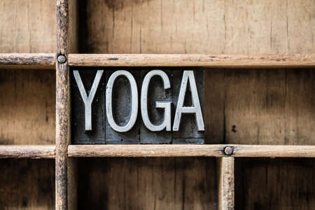 The word YOGA written in vintage metal letterpress type sitting in a wooden drawer. Imagens