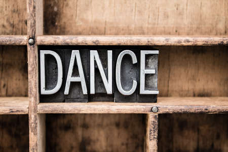 The word DANCE written in vintage metal letterpress type in a wooden drawer with dividers.