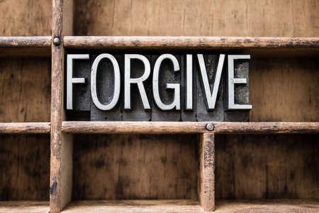 pardon: Le mot �pardonner� �crite en caract�res typographique m�tallique vintage dans un tiroir en bois avec s�parateurs. Banque d'images