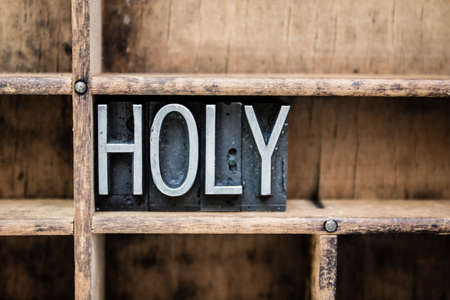 baptize: The word HOLY written in vintage metal letterpress type in a wooden drawer with dividers.