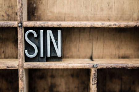 The word SIN written in vintage metal letterpress type in a wooden drawer with dividers.