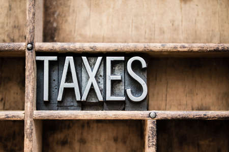 tax bracket: The word TAXES written in vintage metal letterpress type in a wooden drawer with dividers.