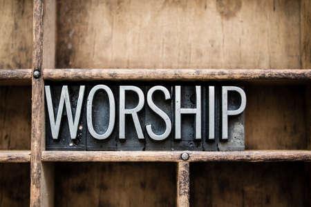 Het woord 'aanbidding' geschreven in vintage metalen boekdruk soort in een houten lade met verdelers.
