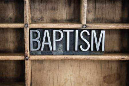 """battesimo: La parola """"battesimo"""", scritto in epoca in metallo di tipo tipografica in un cassetto di legno con divisori."""