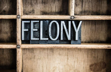 felony: The word FELONY written in vintage metal letterpress type in a wooden drawer with dividers. Stock Photo