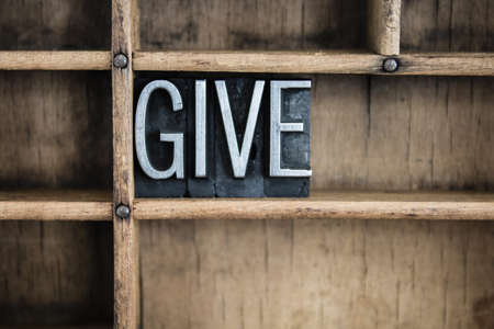 The word GIVE written in vintage metal letterpress type in a wooden drawer with dividers.