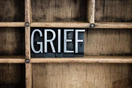 単語「悲しみ」の仕切り付き木製引き出しの中にヴィンテージの金属活版型で書かれました。