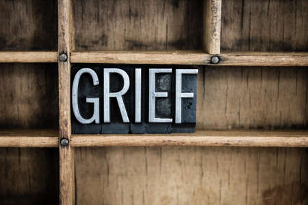 "The word ""GRIEF"" written in vintage metal letterpress type in a wooden drawer with dividers."