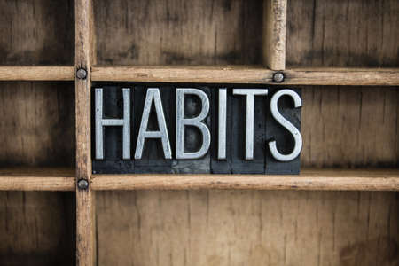 custom cabinet: The word HABITS written in vintage metal letterpress type in a wooden drawer with dividers. Stock Photo